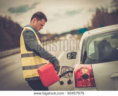 Man refuelling his car on a highway roadside