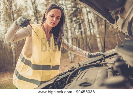 Woman checking oil level on  a roadside