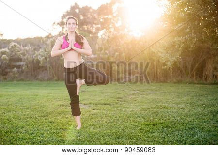 Young woman practicing yoga outside in the grass