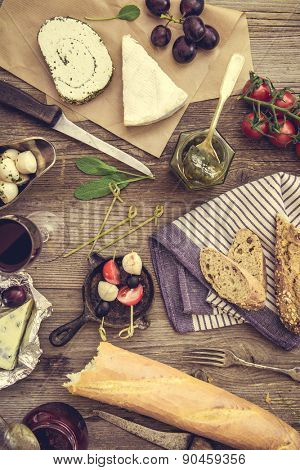 Cheese, wine and other food  ingredients on a wooden table. French snacks on a wooden background.