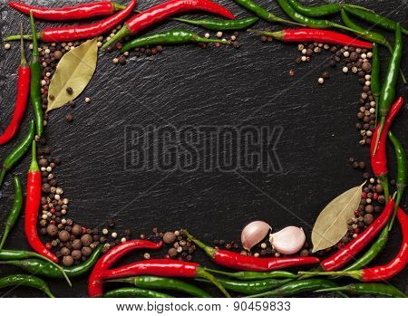 Chili pepper, peppercorn, garlic and bay leaves on black stone. Top view with copy space