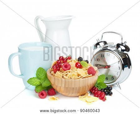 Fresh corn flakes with berries, milk jug, cup and alarm clock. Isolated on white background