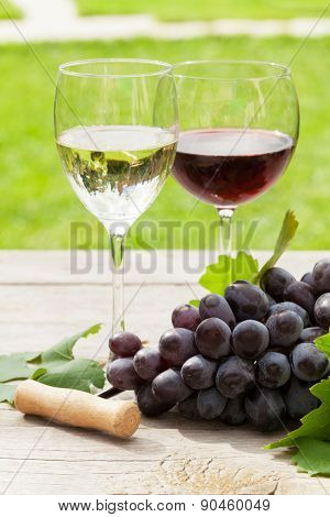 White and red wine glasses and red grape. Focus on grape