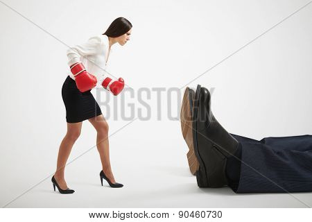 angry businesswoman in boxer gloves looking at big knocked out businessman over light grey background
