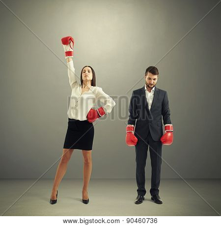 businessman loser and winner businesswoman in red boxing gloves over dark grey background
