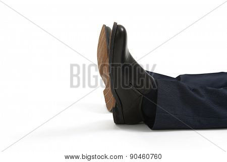 close up of lying mans legs in black shoes. isolated on white background
