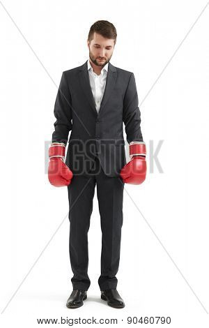 sad businessman in formal wear and red boxing gloves over white background