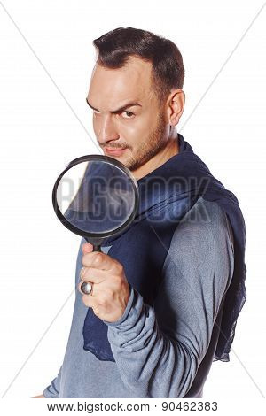 Serious man looking through magnifying glass