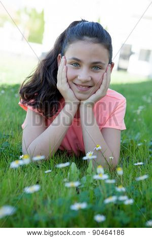 Happy casual preteen girl lying in the grass