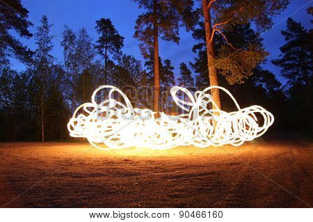 Fire spinning at night in forest