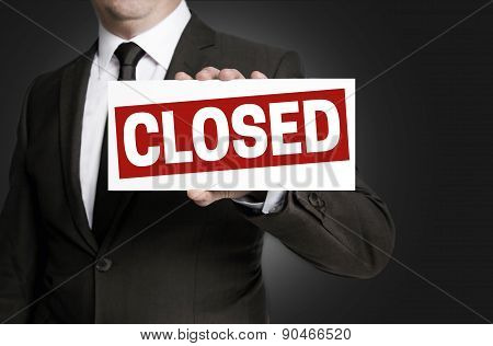 Closed Sign Held By Businessman