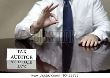 IRS tax auditor business card sitting at desk with hand showing OK sign for audit success