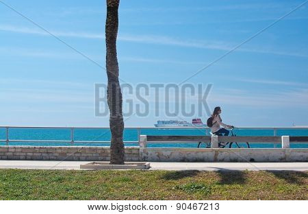 Woman riding a bike along the Paseo Maritimo