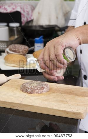 Chef Putting Pepper To Beef Burger /