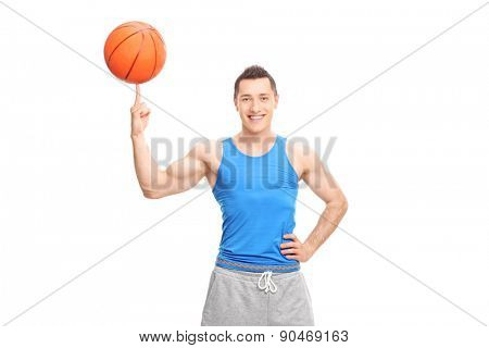 Young cheerful sportsman spinning a basketball on his finger and looking at the camera isolated on white background