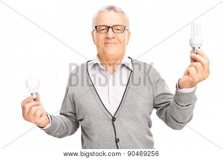 Senior man holding a normal light bulb in one hand and an energy saving light bulb in the other isolated on white background