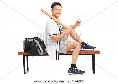 Baseball player holding a baseball bat, sitting on a wooden bench and looking at the camera isolated on white background