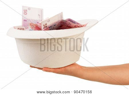 Hand with hat full of money