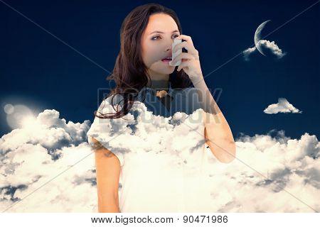 Asthmatic brunette using her inhaler against night sky
