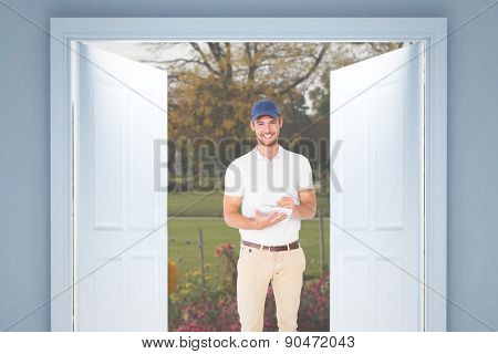 Happy delivery man with cardboard box and clipboard against flowers in a park