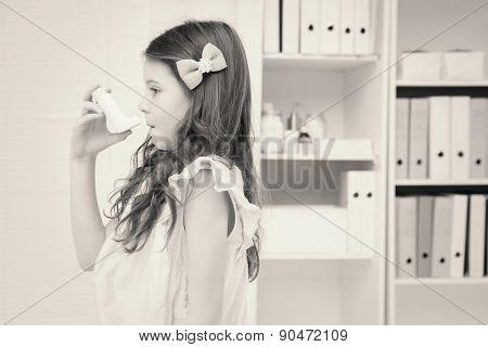 Little girl taking inhaler in medical office