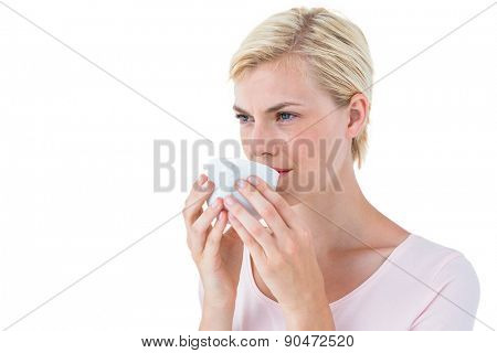 Attractive blonde woman drinking hot beverage on white background