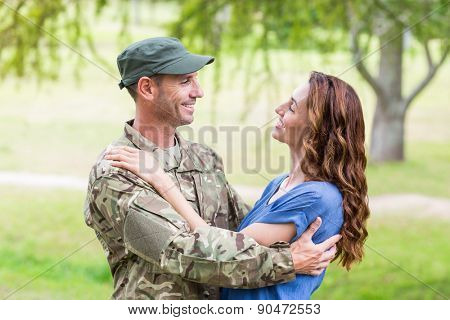 Handsome soldier reunited with partner on a sunny day
