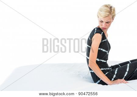 Doubtful blonde woman sitting on bed on white background