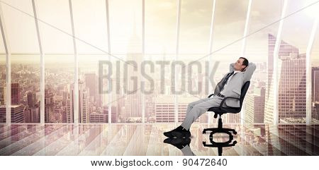 Businessman relaxing in swivel chair against room with large window looking on city