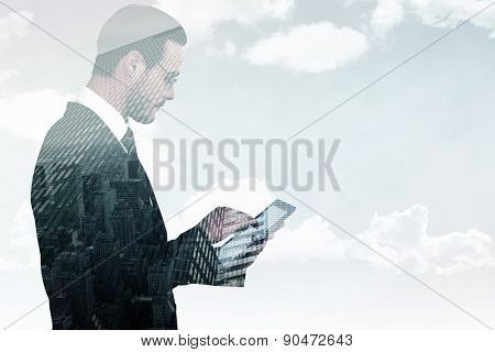 Businessman in reading glasses using his tablet pc against low angle view of skyscrapers