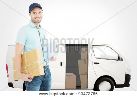 Portrait of happy courier man with parcel against white delivery van