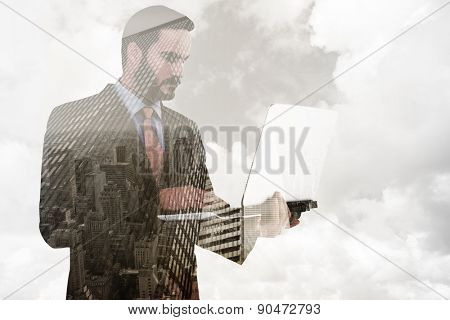 Focused businessman using his laptop against low angle view of skyscrapers