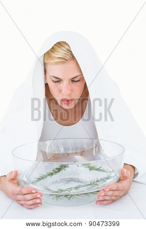 Blonde woman inhaling herbal medicine on white background