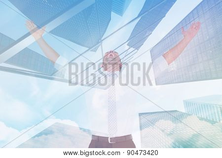Handsome businessman cheering with arms up against skyscraper