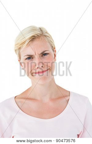 Confused blonde woman looking at camera on white background