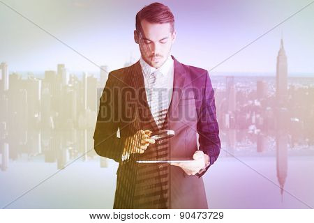 Concentrated businessman using magnifying glass against low angle view of skyscrapers