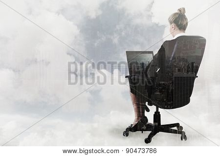 Businesswoman sitting on swivel chair with laptop against new york skyline