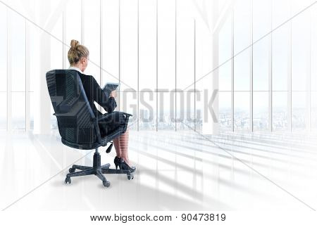 Businesswoman sitting on swivel chair with tablet against room with large window looking on city