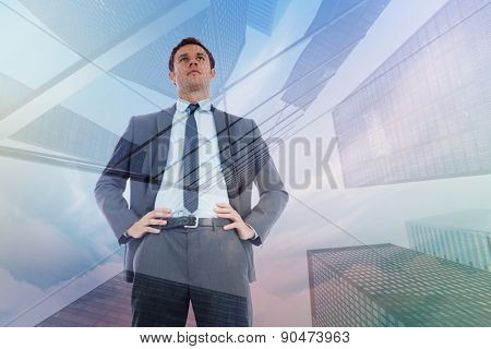 Serious businessman with hands on hips against skyscraper