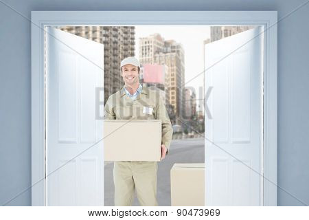 Happy delivery man carrying cardboard box against new york street