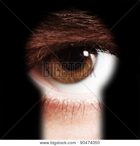 Male Eye Spying Through A Keyhole
