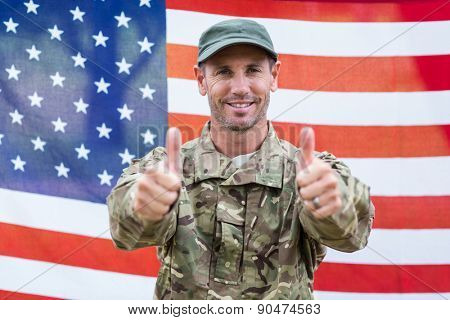 Soldier looking at camera thumbs up against an american flag