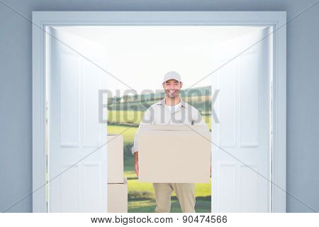 Courier man carrying cardboard box against scenic landscape