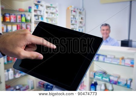 Man using tablet pc against pharmacist with grey hair standing behind shelves of drugs
