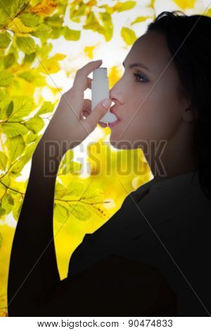 Asthmatic brunette using her inhaler against detail shot of leaves