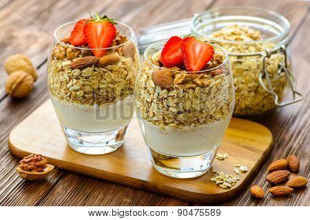 Fresh healthy breakfast of granola, yogurt, nuts and strawberries
