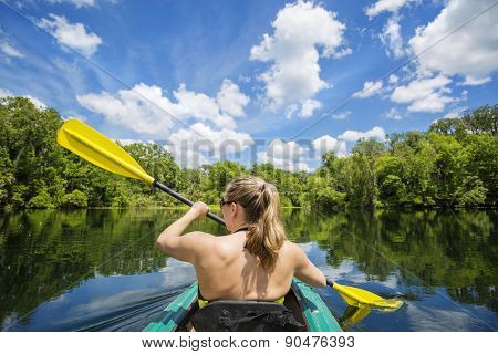 Woman kayaking along a beautiful tropical jungle river. Lots of copy space above and view from behind