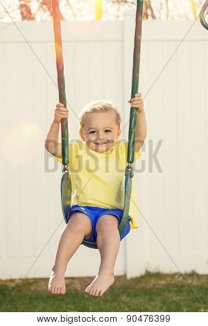 Cute little boy smiling and playing on outdoor swings on a warm summer day
