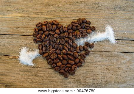 Coffee beans heart stabbed by white sugar