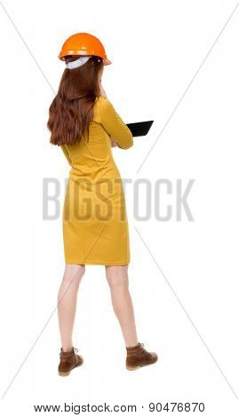 Backview of business woman in construction helmet stands and enjoys tablet or using a mobile phone.   backside view of person.  Isolated over white background. Girl dress in mustard works on computer.